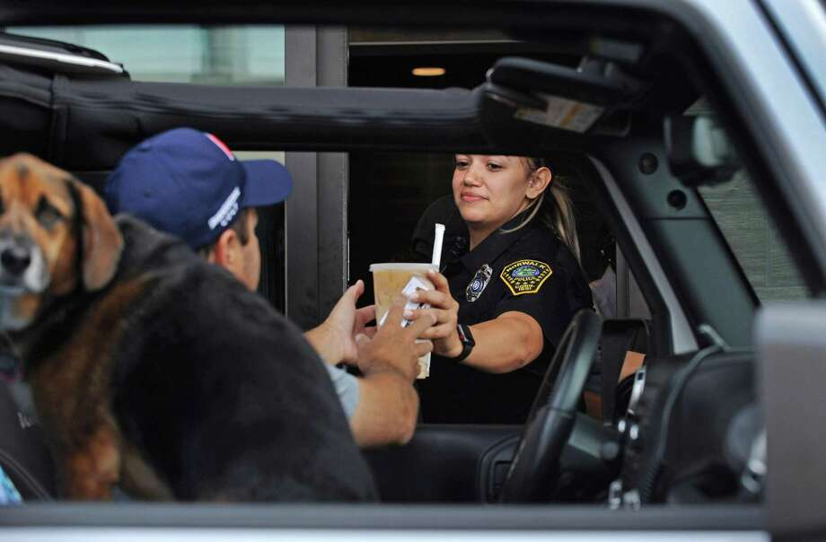 Officer Tiffany Ortiz serves up an iced coffee to Chris Durkin and his dog, Daisy, at the drive-thru as the Norwalk Police Department hosts Coffee with a Cop at McDonald's on Thursday in Norwalk. The idea is to bridge the gap with the public and allow the community to voice concerns and meet with the officers in the community. Photo: Erik Trautmann / Hearst Connecticut Media / Norwalk Hour