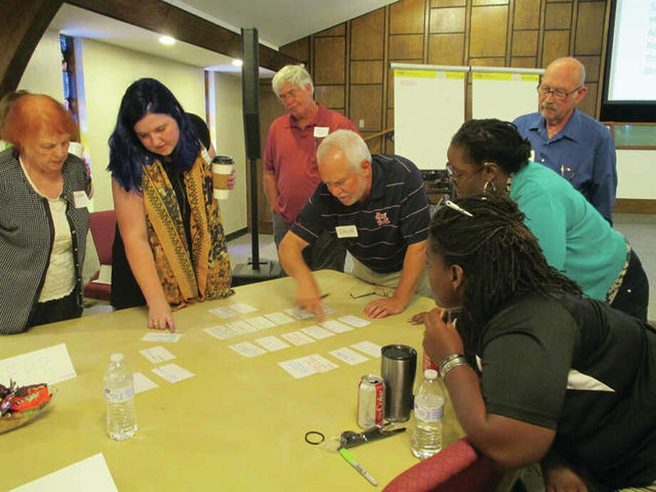 Madison County Community Development Program Coordinator David Harrison (center) works with social service and faith-based organization leaders during a two-day crisis summit earlier this month as they work toward a plan create a new crisis network of connections called Madison County Connected. Photo: For The Intelligencer