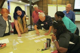 Madison County Community Development Program Coordinator David Harrison (center) works with social service and faith-based organization leaders during a two-day crisis summit earlier this month as they work toward a plan create a new crisis network of connections called Madison County Connected.