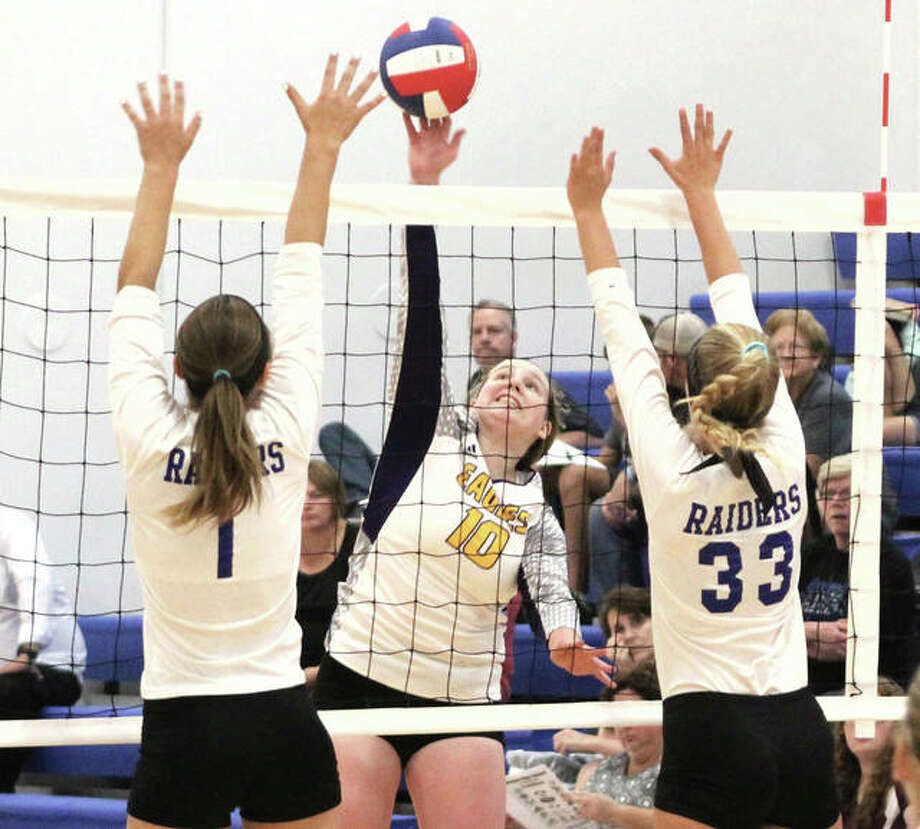 CM's Mackenzie Cato (middle) hits between the block put up by Brussels' Sylvia Baalman (33) and Toni Odelehr during an Aug. 21 match at the Roxana Tournament. Both the Eagles and Raiders dropped matches on Thursday. Photo: Greg Shashack / The Telegraph