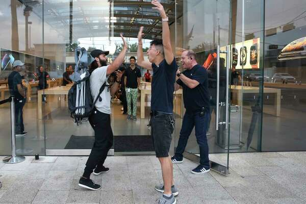 The Highland Village Apple store welcomes first-in-line customer Isaiah Stofferahn to purchase new poducts at 8 a.m. on Friday, Sept. 21, 2018, in Houston. Stofferahn had been waiting in the line since Sunday. The newly released products included iPhone Xs, iPhone Xs Max, iPhone Xr and Watch Series 4.