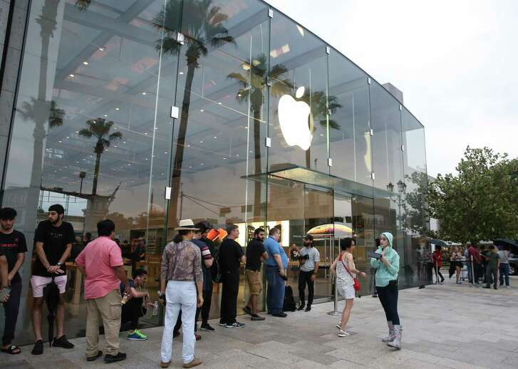 Apple customers wait in the line and ready to purchase the new products at the Highland Village Apple store before the doors open at 8 a.m. on Friday, Sept. 21, 2018, in Houston. The newly released products included iPhone Xs, iPhone Xs Max, iPhone Xr and Watch Series 4.