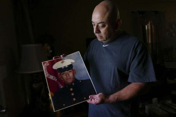 Retired Marine Gunnery Sgt. Enrique Martinez of San Antonio applied for a passport late last year, submitting a birth certificate showing that he's an American citizen. Not long after, a State Dept. letter informed him that his birth certificate wasn't enough to prove he was a citizen. He holds a photograph of himself as an 18-year-old young Marine.