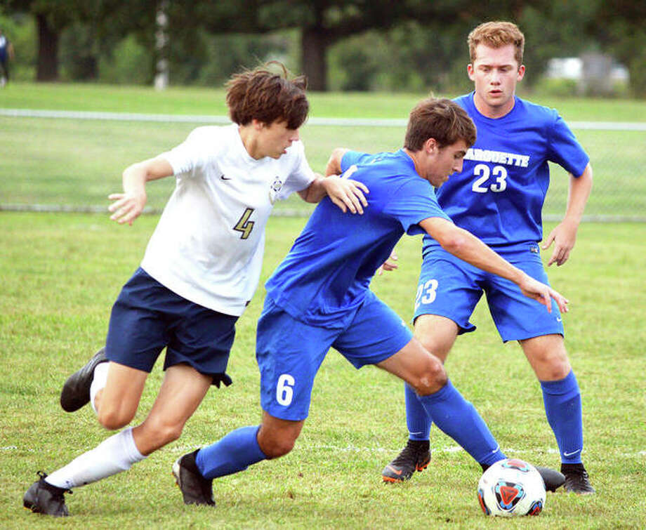 Marquette Catholic's Noah McClintock (middle) controls the ball against defensive pressure from Father McGivney's Joey Crowder (left) while the Explorers' Nathan Joehl backs up the play during a Aug. 30 match in Alton. The Explorers were back on their home field at Moore Park Thursday and pushed their record to 9-0-3 with a victory over Freeburg. Photo: Scott Marion / Hearst Illinois