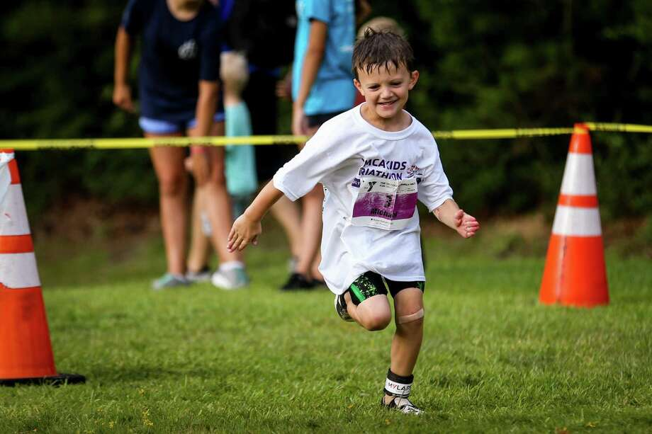 Michael Reardon, 6, smiles as he pushes through the running portion of the YMCA Kids Triathlon on July 21 at The Woodlands Family YMCA. Photo: Michael Minasi, Staff Photographer / Houston Chronicle / © 2018 Houston Chronicle