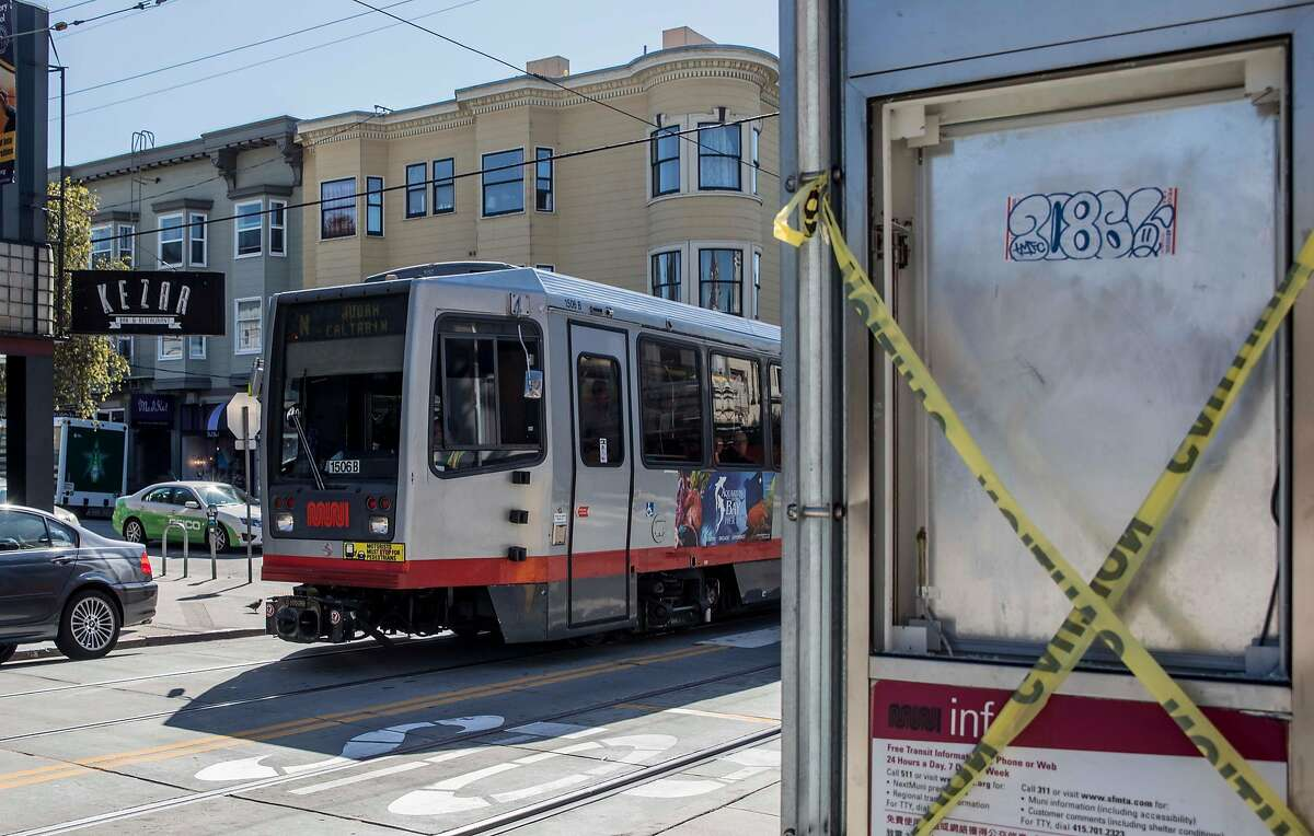 A vandalized Muni bus shelter is seen as an N-Judah train moves through the intersection of Carl and Cole streets in the Cole Valley neighborhood of San Francisco, Calif. Thursday, September 20, 2018.