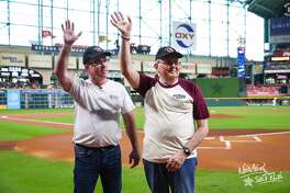 Kingwood resident Merlin Moseman (right) and Michael Tuoy (left) wave to Astros fans from the field at Minute Maid Park before the baseball game on Sunday, Sept. 16.