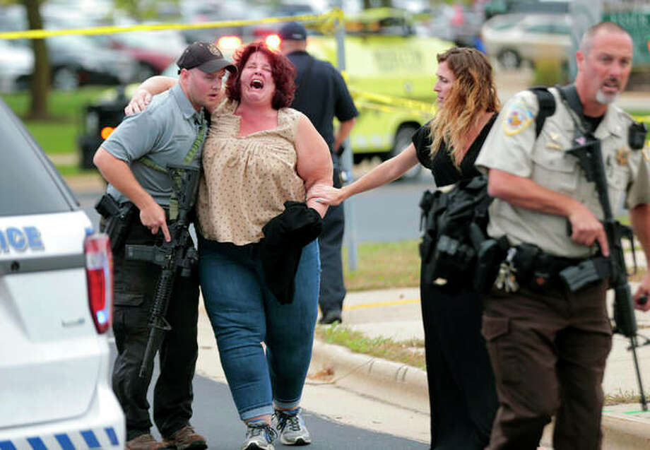 A woman is escorted from the scene of a shooting at a software company in Middleton, Wisconsin, Wednesday. Four people were shot and wounded during the shooting in the suburb of Madison, according to a city administrator. Photo: Steve Apps | Wisconsin State Journal (AP)