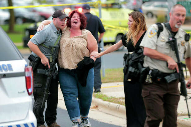 A woman is escorted from the scene of a shooting at a software company in Middleton, Wisconsin, Wednesday. Four people were shot and wounded during the shooting in the suburb of Madison, according to a city administrator.