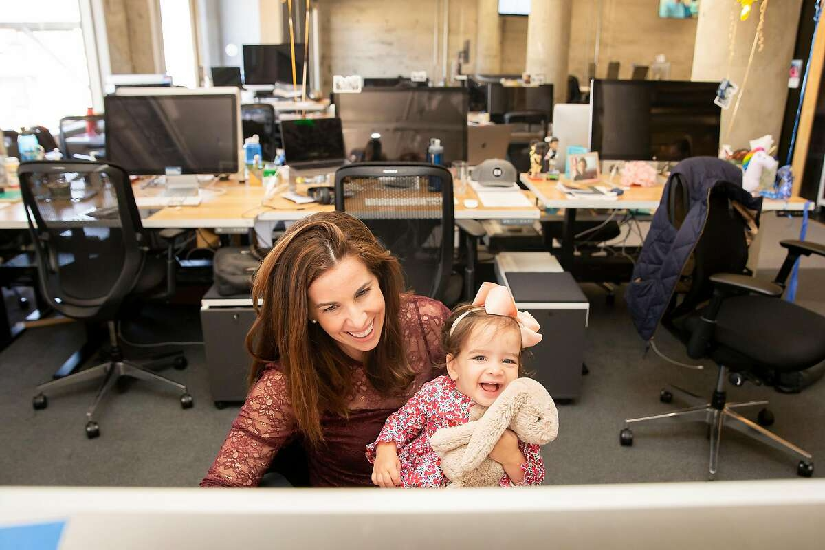 Morgan Mohun-Gholson sits at her desk with her daughter Chloe Gholson, 1, at Pinterest's headquarters San Francisco on Sept. 20, 2018. Mohun-Gholson, a working mom at Pinterest, used Milk Stork to transport her breast milk back to her daughter when she traveled for work. The Palo Alto-based company handles the logistics of transporting breast milk for working moms while they are nursing and working away from home.