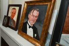 Portraits of John Frank Sr. rest on the mantle of the Frank home in Norwalk. Frank, who died in 2016, will be honored with the placement of a memorial at Calf Pasture Beach early Monday evening, Sept. 24.
