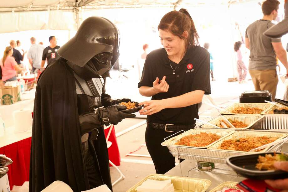 Lena Shannon, with Pei Wei, serves a plate of food to a performer dressed as Darth Vader during the Taste of the Village event in October 2016 in the H-E-B parking lot on the Woodlands Parkway and Kuykendahl Road. Photo: Michael Minasi, Staff / Chronicle / © 2016 Houston Chronicle