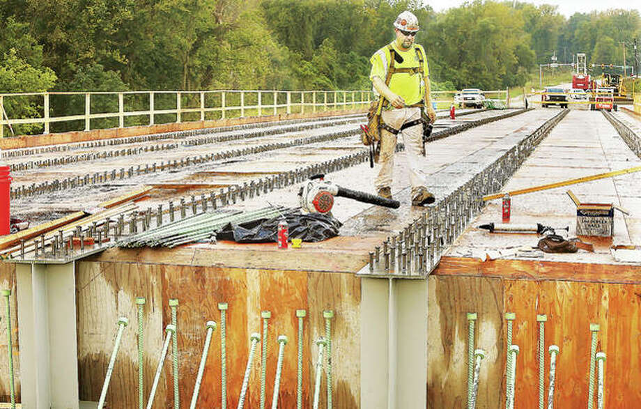 A worker walks across the plywood and steel I-beams of the new Illinois Route 143 bridge over Indian Creek Wednesday as the bridge draws nearer to having its concrete deck surface poured. Route 143, the primary east/west roadway between Wood River and Edwardsville, has been closed for months. Photo: John Badman | The Telegraph