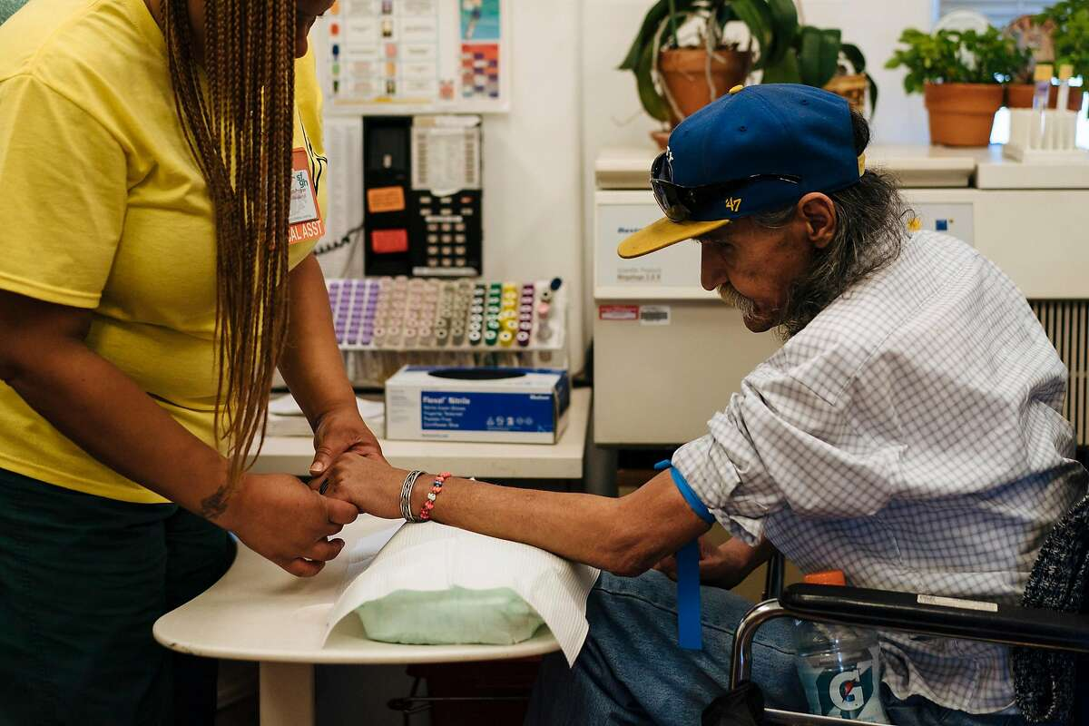 HIV Medical Assistant, Ayafemi Wilson, extracts blood from Richard Ramirez, 67, during a check up at the San Francisco General Hospital's Division of HIV/AIDS, Ward 86 in San Francisco, Calif., on Thursday, Sept. 20, 2018.