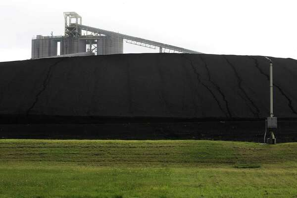 A conveyor belt is seen above a pile of coal at the local J.T. Deely coal-fired power plant. The plant will be shut down. But the climate question must be addressed at the national level, too.