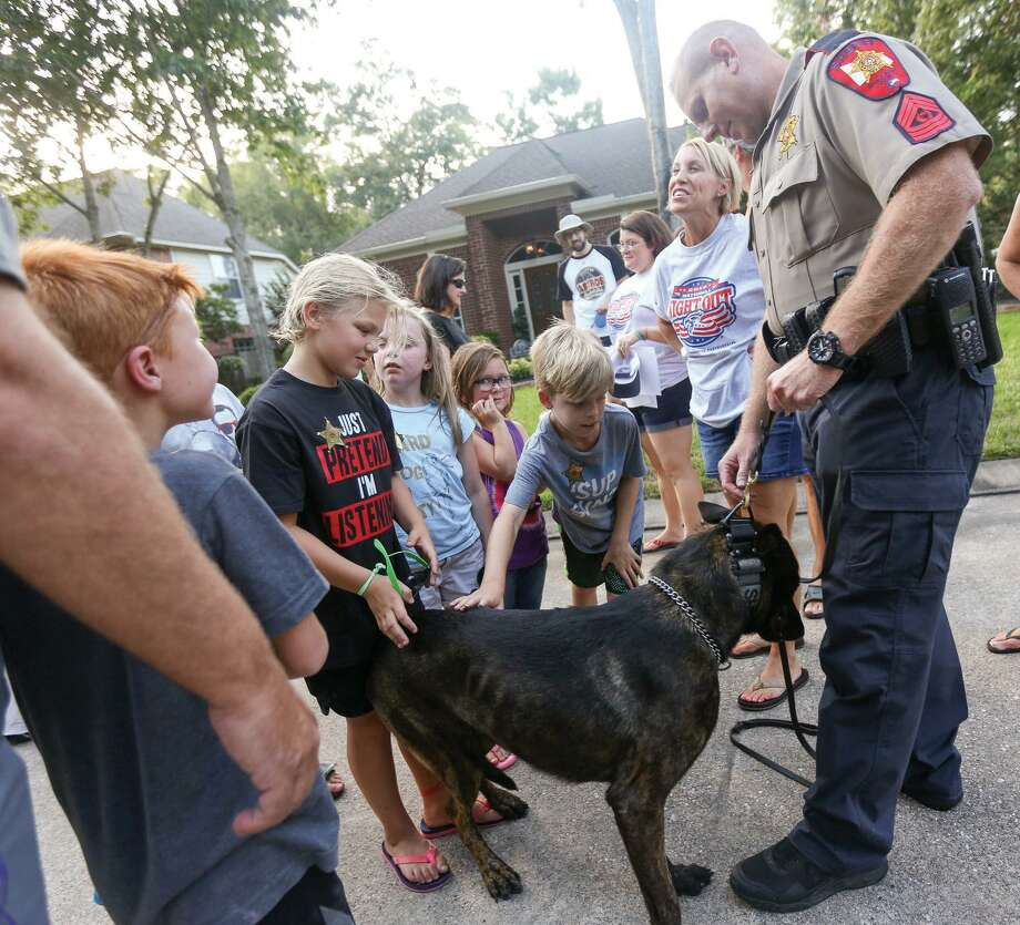 Sgt. David Birch, Montgomery County Sheriffs Office, steadies 3-year-old K-9 police dog, Hummer, as residents gather to pet him during the National Night Out event on Tuesday, Aug. 2, 2016, on Silver Crescent Circle in The Woodlands. This year, parties are to be held Sunday, Oct. 14. Packet Pick-Up day is Thursday, Sept. 27 from 10 a.m. to 6 p.m. at The Woodlands Township town hall at 2801 Technology Forest Blvd. Photo: Michael Minasi, Photographer
