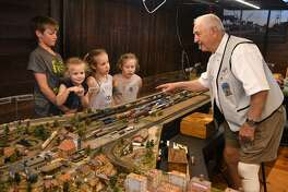 "Matthew Uzzell, 13, from left, of Magnolia, and his sisters Saige, 5, Jolee, 10, and Julia, 7, check out the Z- scale Golden-Blackhawk & Central City Railroad train model of David ""Mister Dave"" George' of Spring, on display inside the 1907 Depot Museum in Tomball on July 3, 2018. (Jerry Baker/For the Chronicle)"