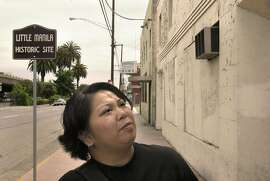 "MANILA24010LH.jpg  Many of the Filipino-Americans living in the West came to the U.S. through Stockton.  Now, descendants of Filipinos who immigrated to the U.S. in the first half of the 20th century are fighting to save Stockton's once-vibrant Filipino ethnic community, called Little Manila.  Dawn Mabalon looking at this building (with air conditioner on wall) which used to be the ""Rizal Social Club"" as well as a Filipino Boxing Ring.   Shot on 6/18/03 in Stockton.  LIZ HAFALIA / The Chronicle"