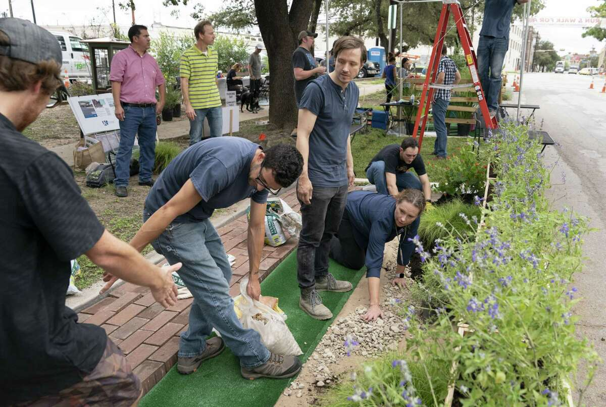 San Antonio River Authority employees prepare a small park with permeable pavement, bioretention features and native plants on Friday along McCullough Avenue. Their work was part of the national PARK(ing) Day event, which transforms concrete parking spaces into small parks in an effort to make urban spaces more inviting and walkable.