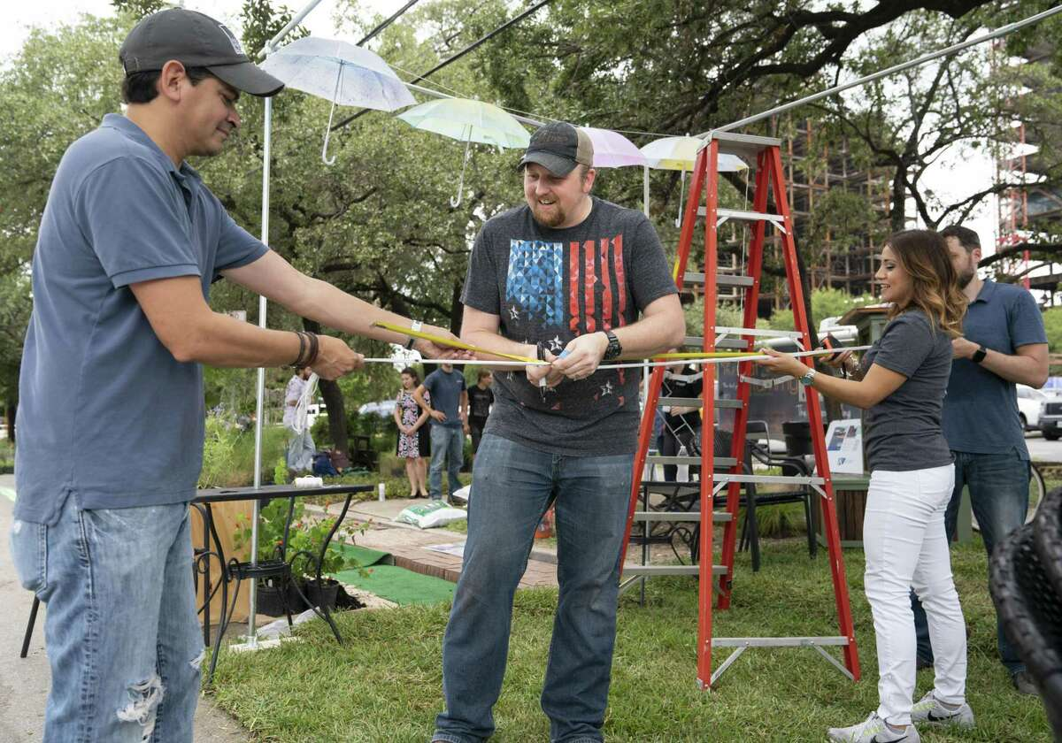 Ford, Powell & Carson architect Oscar Reyes (left) helps designers Jeremy Kreusel (center) and Michelle Garcia set up the firm's tiny urban park along McCullough Avenue downtown. The display was part of the national PARK(ing) Day event, which transforms concrete parking spaces into small parks in an effort to make urban spaces more inviting and walkable.