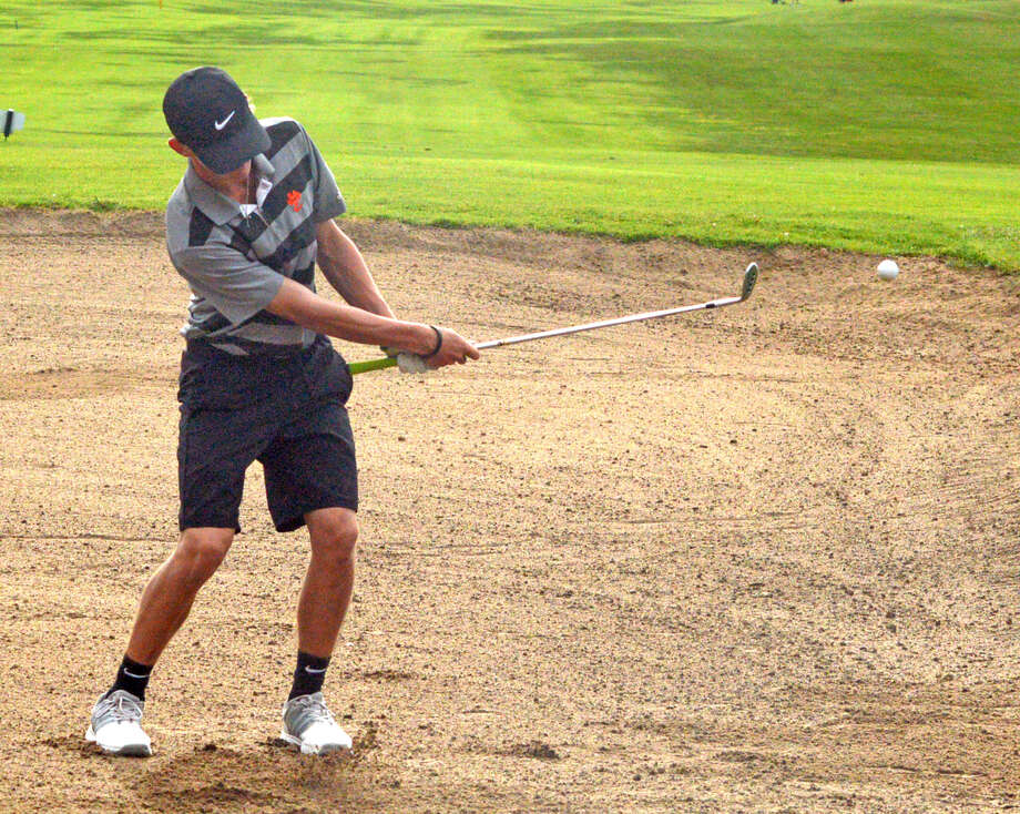 Edwardsville sophomore Hayden Moore hits out of a sand trap on Friday on hole No. 17 at Oak Brook Golf Club during the Dick Gerber Invitational. Photo: Scott Marion