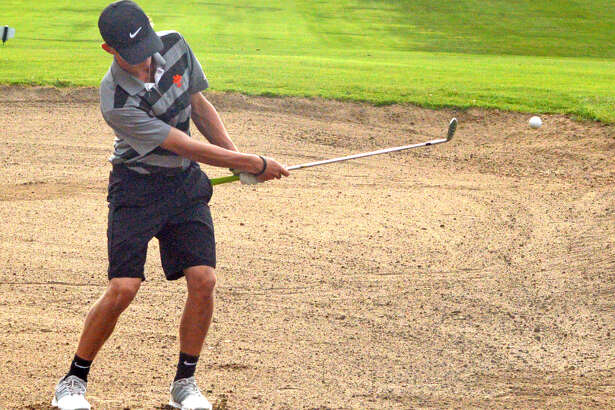 Edwardsville sophomore Hayden Moore hits out of a sand trap on Friday on hole No. 17 at Oak Brook Golf Club during the Dick Gerber Invitational.