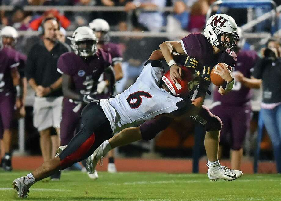 North Haven's Nick Dodge, right, escapes a tackle attempt by Cheshire cornerback Christian Russo on a touchdown run Friday night in North Haven. Photo: Catherine Avalone / Hearst Connecticut Media / New Haven Register