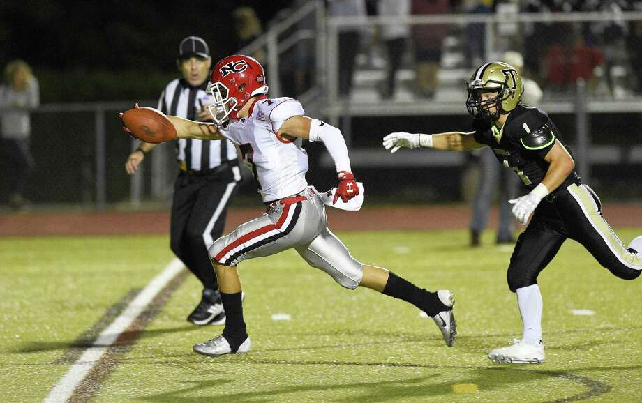 New Canaan's Zach LaPolice (7) stretches the ball in for a touchdown as he runs past Trumbull's Raymond Leonzi during an FCIAC football game in Trumbull, Conn. on Sept. 21, 2018. New Canaan defeated Trumbull 48-7. Photo: Matthew Brown / Hearst Connecticut Media / Stamford Advocate