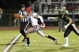 New Canaan's Zach LaPolice (7) stretches the ball in for a touchdown as he runs past Trumbull's Raymond Leonzi during an FCIAC football game in Trumbull, Conn. on Sept. 21, 2018. New Canaan defeated Trumbull 48-7.