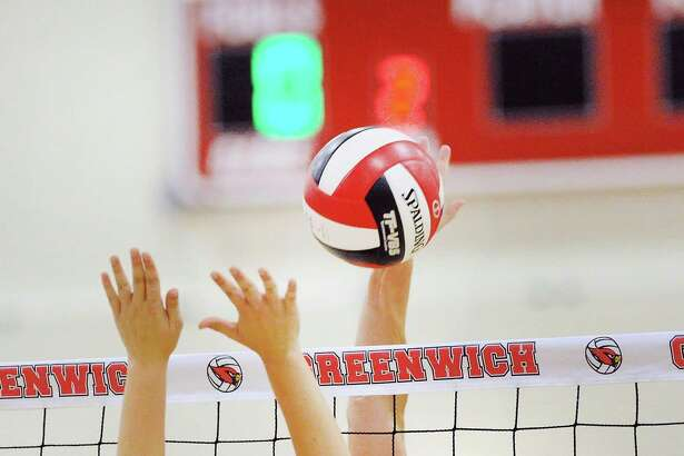 Greenwich's Caroline Mrdelja (15) spikes the ball against Darien during a volleyball match Friday at Greenwich High School. The Cardinals won 3-2.