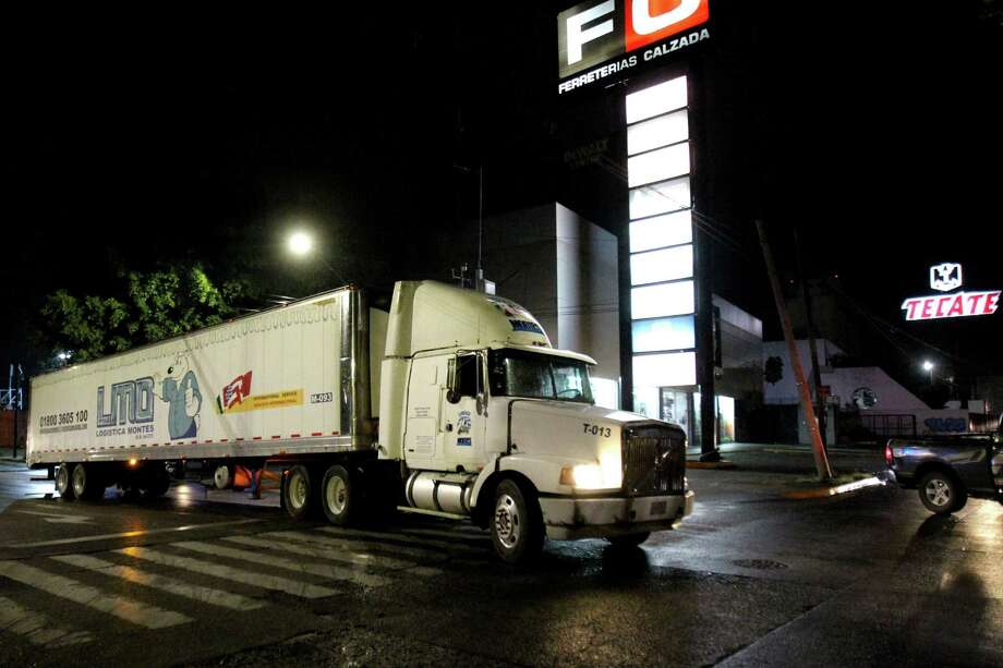 A trailer that carries more than 100 bodies of unidentified people is driven through the streets of Guadalajara after being taken from the winery of the prosecutor's in Guadalajara and transferred to the Jaliscience Institute of Forensic Sciences in Tlaquepaque, on Sptember 17,  2018. - Mexican authorities were scrambling to find a parking spot Monday for a truck carrying more than 100 unidentified bodies whose fetid smell has been infuriating residents in the city of Guadalajara. The refrigerated trailer -- rented when morgues in the country's second-largest city hit full capacity -- was parked for two weeks at a warehouse in the downtrodden neighborhood of Duraznera, on the city outskirts, until residents complained of the stench and the flies it attracted. . (Photo by Ulises Ruiz / AFP)ULISES RUIZ/AFP/Getty Images Photo: Ulises Ruiz /AFP /Getty Images / AFP or licensors