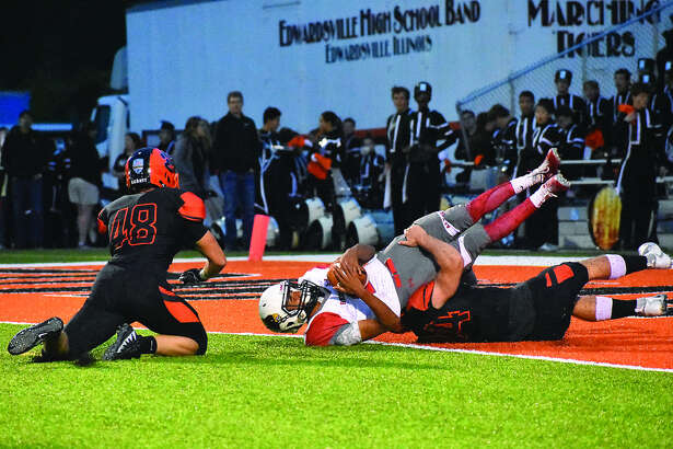 Edwardsville linebacker Jackson Morrissey, bottom, brings down Alton quarterback Andrew Jones for an 18-yard loss after a botched snap on the second play of the game. Jones was ruled down at the 1-yard line.