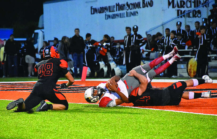 Edwardsville linebacker Jacob Morrissey, bottom, brings down Alton quarterback Andrew Jones for an 18-yard loss after a botched snap on the second play of the game. Jones was ruled down at the 1-yard line. Photo: Matthew Kamp