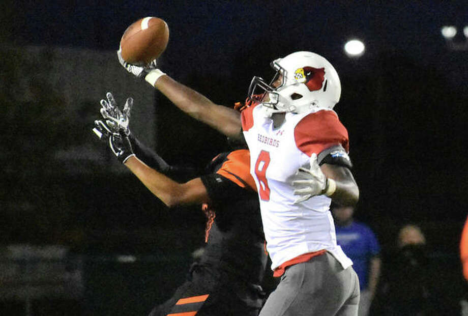 Alton wide receiver Terrance Walker (8) leaps above an Edwardsville defender to make a spectacular one-handed catch for a 48-yard gain during the first quarter Friday night at the District 7 Sports Complex in Edwardsville. Photo: Matthew Kamp / Hearst Illinois