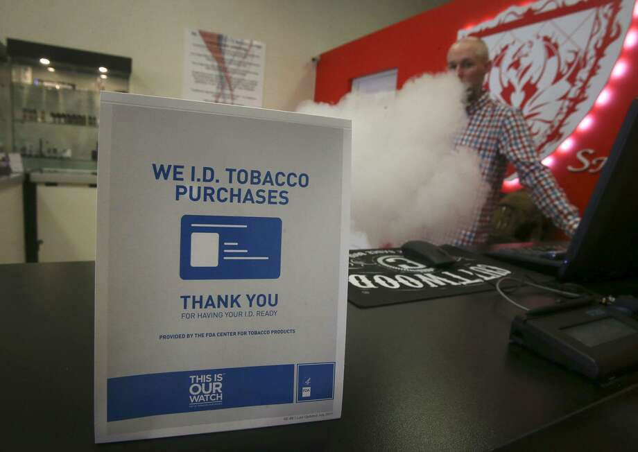 A sign on the counter at the Smoke to Live vape shop at 18154 Blanco Road reminds customers Thursday April 19, 2018 that tobacco products cannot be sold to people under the age of 18. Retailers, convenience stores, and smoke shop owners are preparing for the October 1 implementation of San Antonio's ordinance raising the tobacco buying age to 21. Vaping (right, background) is store manager Jordan Studer. Photo: John Davenport, STAFF / San Antonio Express-News / ©John Davenport/San Antonio Express-News