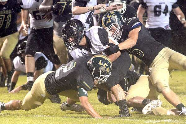 Vidor's Brad Nunez is stopped by Little Cypress-Mauriceville's defense, including Justin Lee (bottom), during their match-up Friday night at LC-M. Friday, September 21, 2018 Kim Brent/The Enterprise