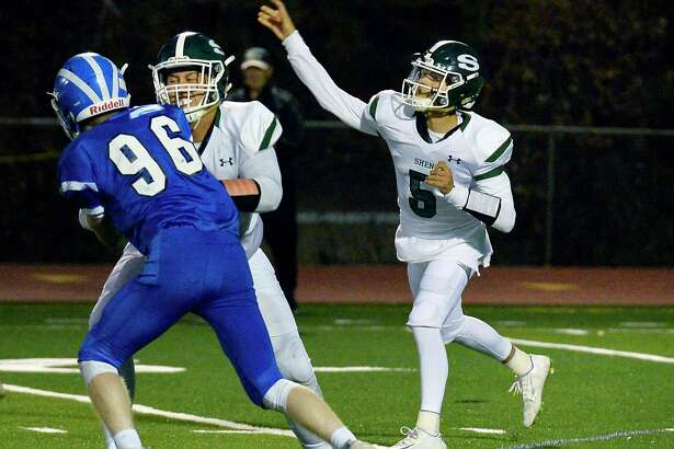 Shenendehowa QB #5 Brendan Belot fires off a pass as #66 Dylan Blowers blocks Shakers' 96 Xavier Mein, left, during Friday night's game Sept. 21, 2018 in Colonie, NY. (John Carl D'Annibale/Times Union)