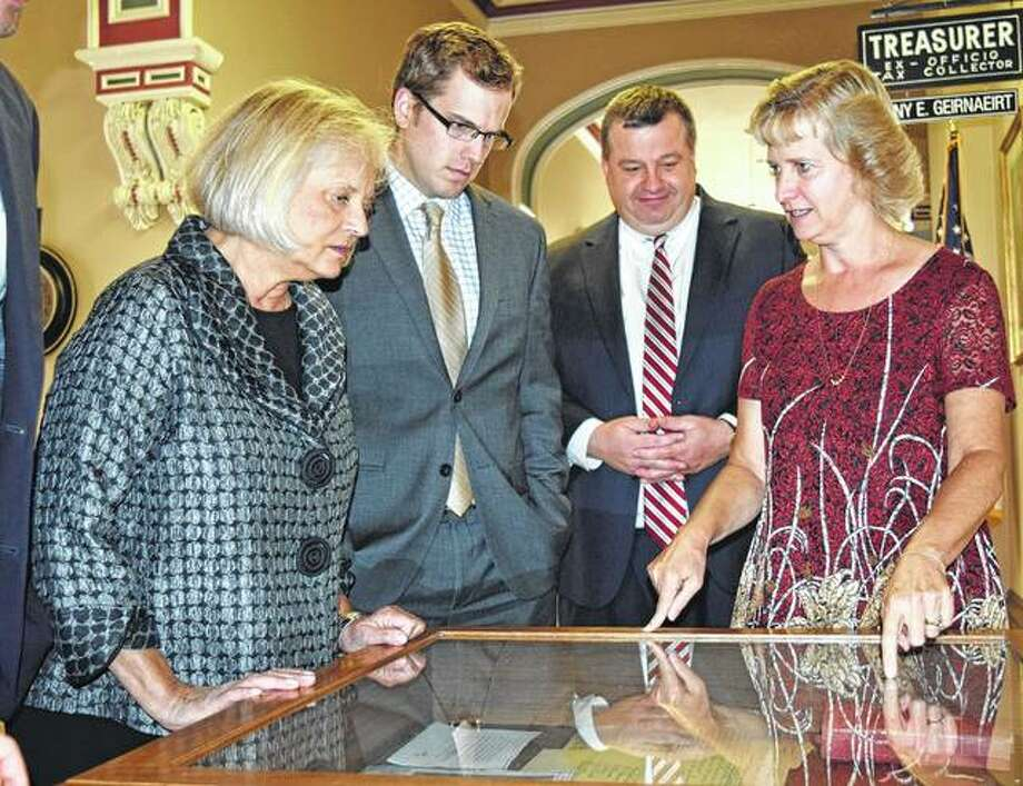 Illinois Appeals Court Judge Aurelia Pucinski (from left) checks out a display of historic court cases Friday at the Morgan County Courthouse along with Assistant State's Attorney Craig Miller, State's Attorney Gray Noll and Circuit Clerk Amy Sipes. Sipes and Miller collected the information for the display, which is part of the Illinois Supreme Court Historic Preservation Commission's county-by-county celebration for the state's bicentennial.