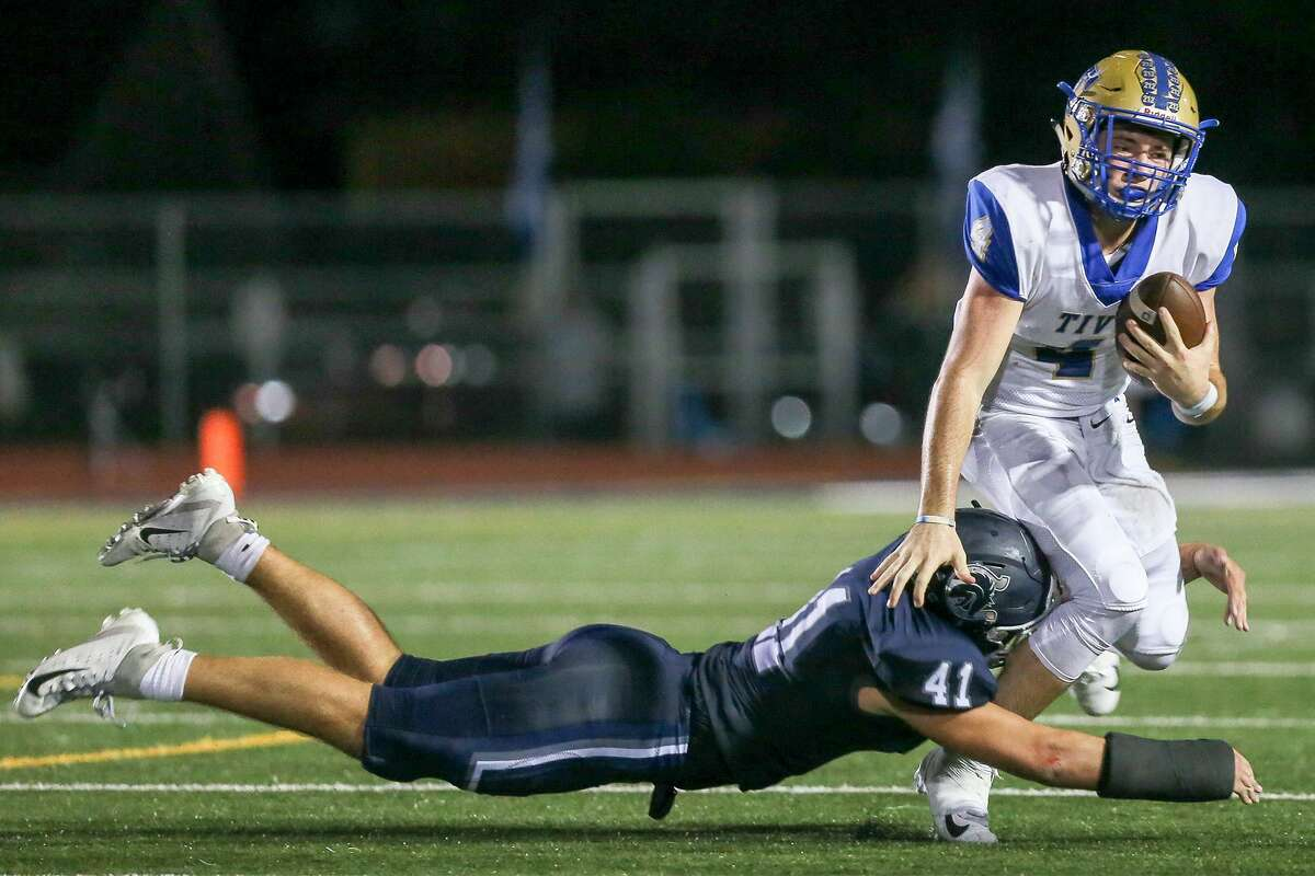 Boerne Champion's Gage Oefinger (left) dives to bring down Kerrville Tivy's Cole Miears during the first half of their high school football district 14-5A-II game at Boerne Stadium on Friday, Sept. 21, 2018.