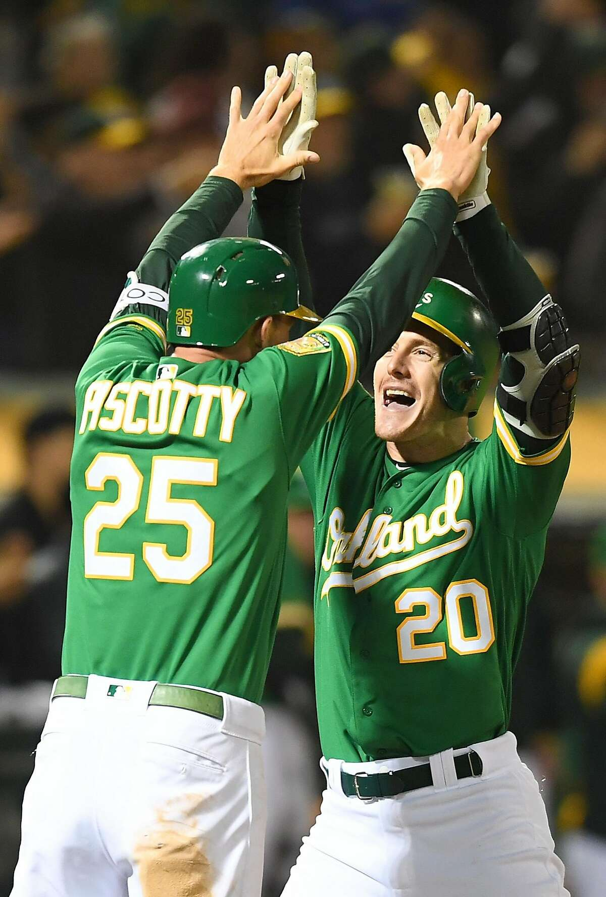 OAKLAND, CA - SEPTEMBER 21: Mark Canha #20 and Stephen Piscotty #25 of the Oakland Athletics celebrates after Canha hit a two-run home run against the Minnesota Twins in the bottom of the six inning at Oakland Alameda Coliseum on September 21, 2018 in Oakland, California. (Photo by Thearon W. Henderson/Getty Images)