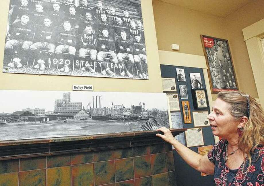 Staley Museum director Laura Jahr shows a vintage team photo of the Decatur Staleys and a photo of the team's stadium, both taken in 1920. Photo: Jim Bowling | Herald & Review