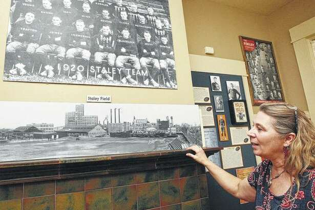 Staley Museum director Laura Jahr shows a vintage team photo of the Decatur Staleys and a photo of the team's stadium, both taken in 1920.