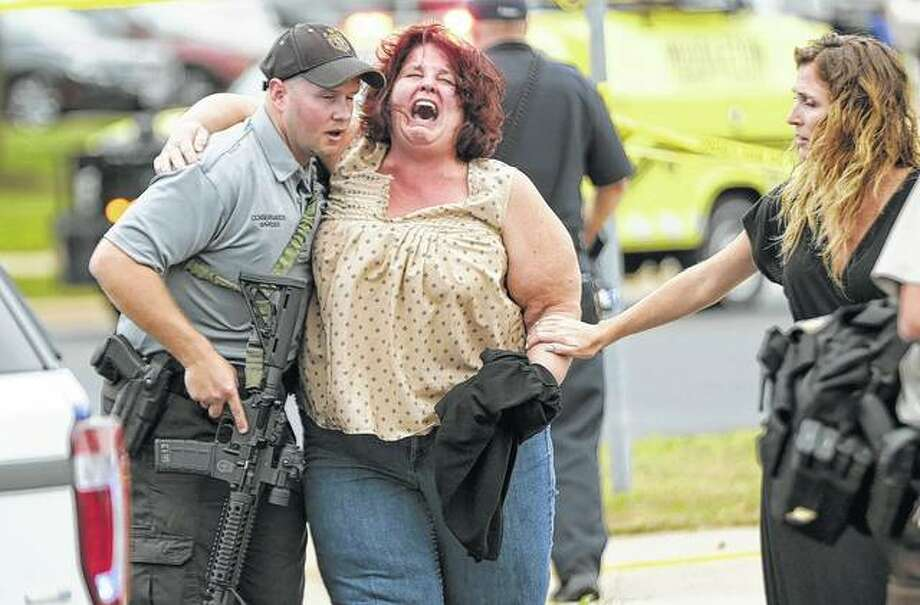 A woman is escorted from the scene of a shooting Wednesday at a software company in Middleton, Wisconsin. Four people were shot and wounded during the shooting. Photo: Steve Apps | Wisconsin State Journal (AP)