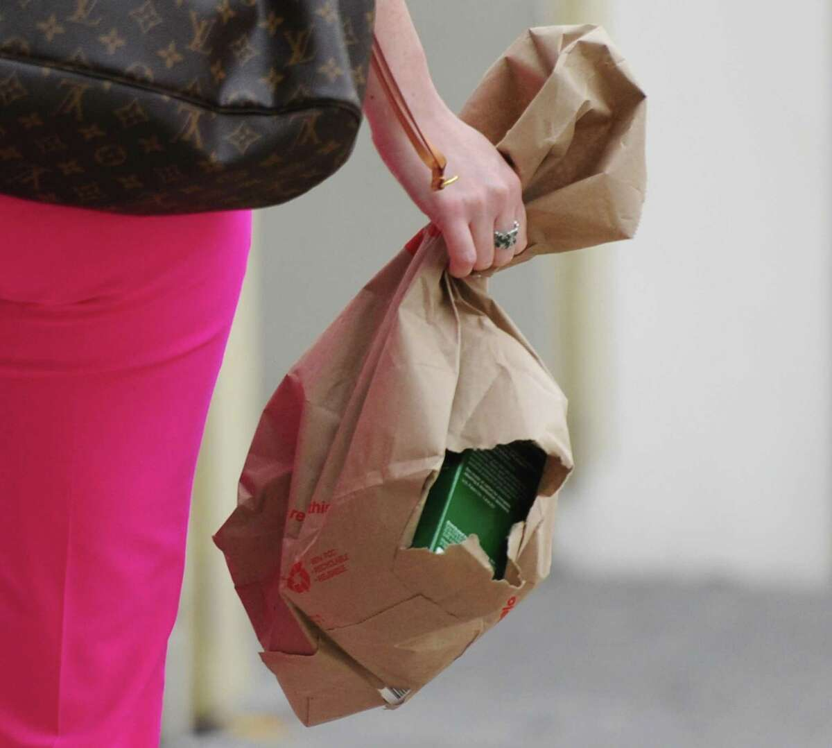 A woman carries items in a paper bag with a hole in it down Greenwich Avenue on Wednesday.
