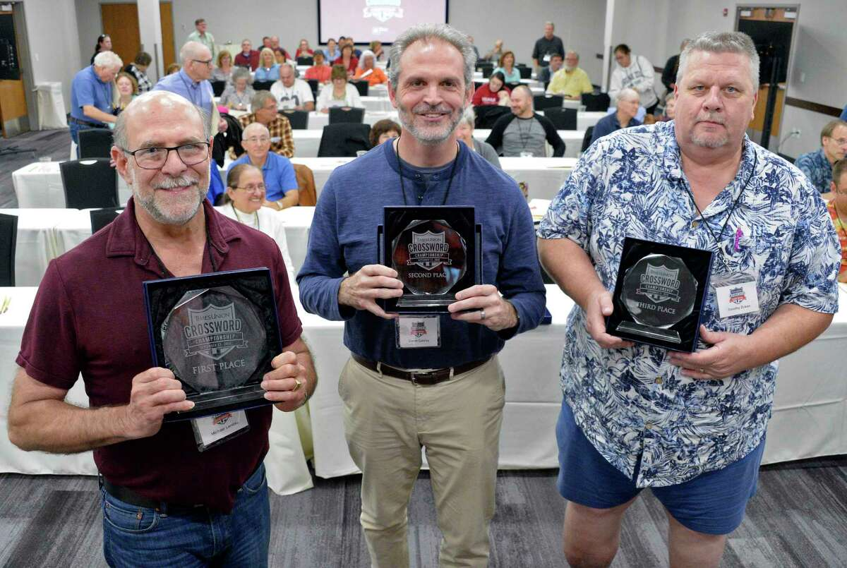 Winners of the inaugural Times Union Crossword Championship, from left, first-place winner Michael Landau of Clifton Park, second-place's Darrin Conroy of East Greenbush, and third-place winner Timothy Zukas of Burnt Hills, pose with their trophies at the Hearst Media Center on Saturday Sept. 22, 2018 in Colonie, NY. (John Carl D'Annibale/Times Union)