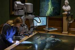 "In this Thursday, Sept. 20, 2018, photo The Huntington's senior paintings conservator, Christina O'Connell, examines ""The Blue Boy"" painting, made around 1770 by the English painter Thomas Gainsborough (1727-1788), through a Haag-Streit surgical microscope at ""Project Blue Boy"" exhibit in the Thornton Portrait Gallery at The Huntington in San Marino, Calif. Beginning Saturday, Sept. 22, visitors to The Huntington Library, Art Collections and Botanical Gardens can see conservator Christina O�Connell repair Thomas Gainsborough�s priceless portrait of a boy dressed all in blue. (AP Photo/Damian Dovarganes)"