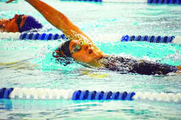 Edwardsville's Josie Bushell competes in the backstroke leg of the 200-yard individual medley race during a triangular against Springfield and Springfield Sacred Heart-Griffin on Saturday at the Chuck Fruit Aquatic Center.
