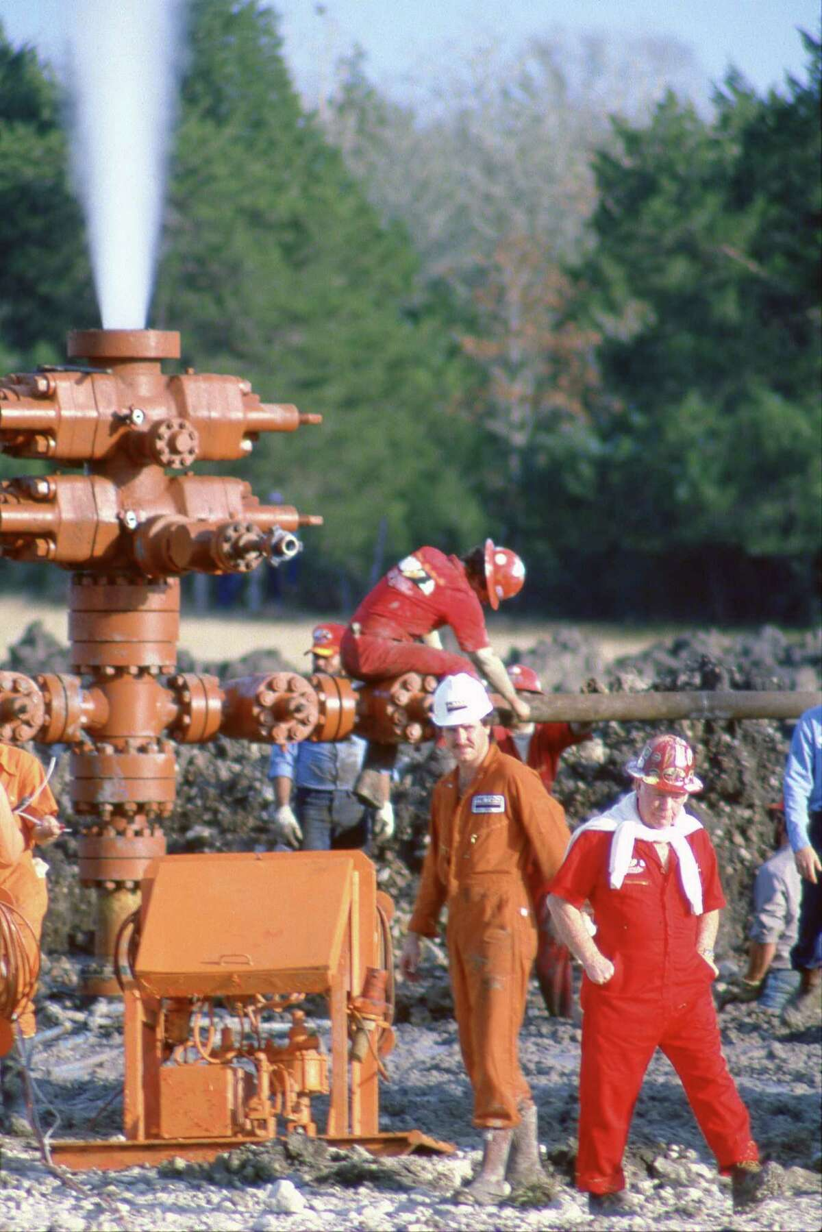 12/19/1984 - Red Adair, at right in red and white, and his firefighting crew extinguish a gas well blow-out near Round Top. Cedar Hill Petroleum Co. are the operators of the well.