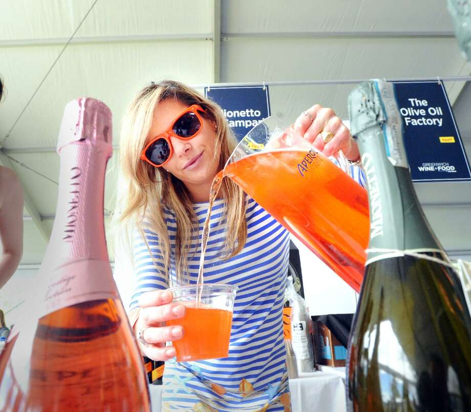 Greenwich resident Annabelle Berizzi of Mionetto & Campari pours an Aperol drink during the annual Greenwich Wine + Food Festival at Roger Sherman Baldwin Park in Greenwich, Conn., Saturday, Sept. 22, 2018. The multi-day culinary, beverage and entertainment event is a showcase for local restaurants food purveyors and the beverage industry. It is also a fund-raiser for organizations including the Multiple Myeloma Research Foundation, the Town of Greenwich Parks & Recreation Foundation and Ment'or. Photo: Bob Luckey Jr. / Hearst Connecticut Media / Greenwich Time