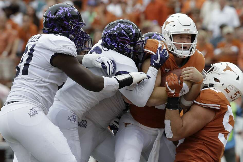 Texas quarterback Sam Ehlinger, second from right, is hit as he runs against TCU during the first half of an NCAA college football game, Saturday, Sept. 22, 2018, in Austin, Texas. (AP Photo/Eric Gay)